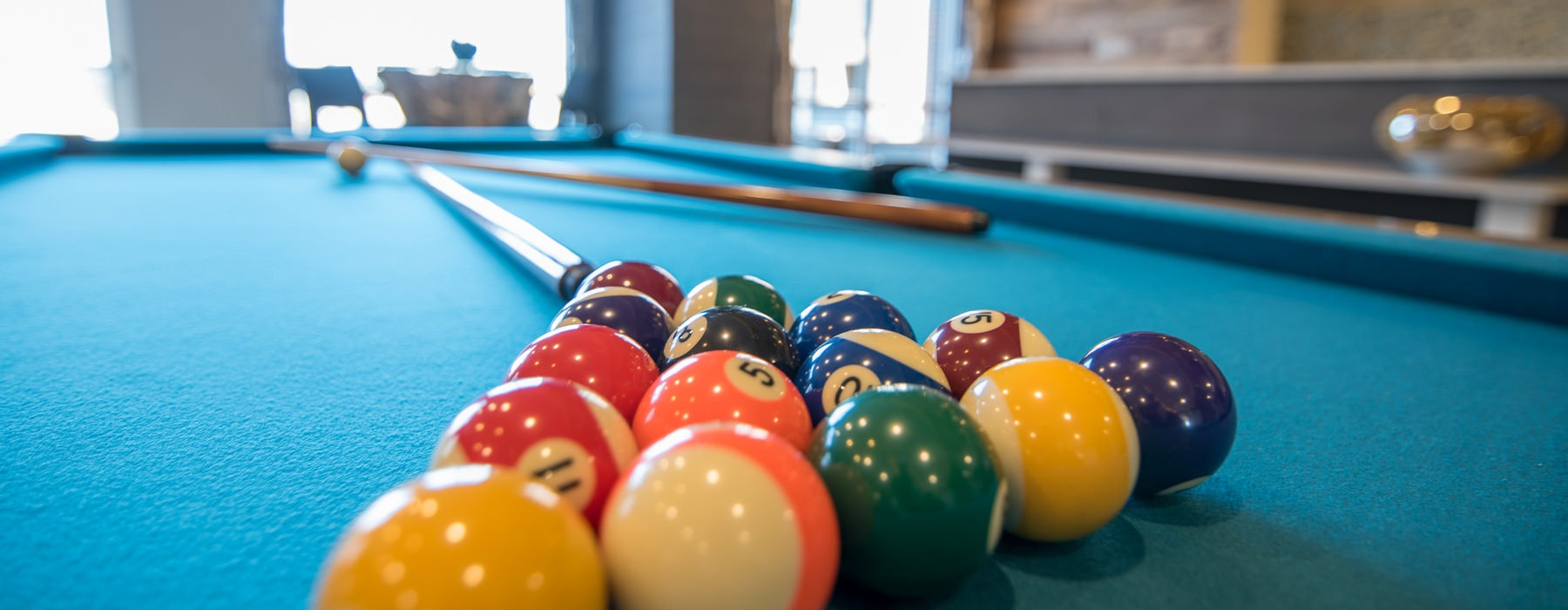 Billiards balls set up for a game on a blue pool table